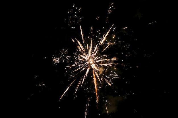 Fogos de artifício dourados e amarelos contra o céu escuro. fogo de artifício em homenagem ao feriado, ano novo, natal de 2017. lindos e grandes fogos de artifício no céu noturno