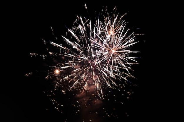 Fogos de artifício explodindo no céu noturno espalhando uma atmosfera festiva