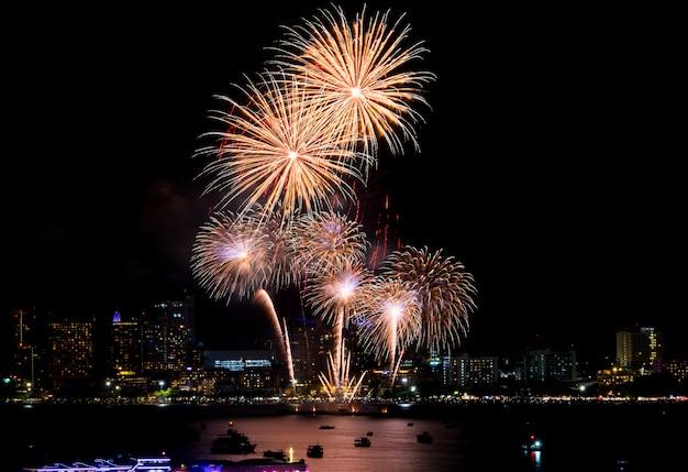Fogos de artifício explorados ao longo da paisagem urbana à noite no porto marítimo