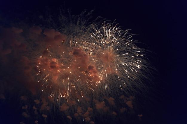 Fogos de artifício multicoloridos borrados iluminam o céu escuro da noite