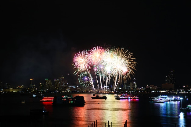 Fogos de artifício multicoloridos na praia e reflexo na superfície da água