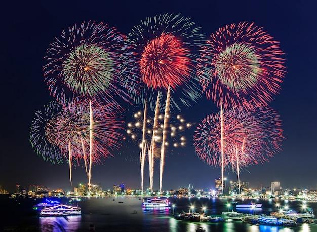 Fogos de artifício sobre a paisagem urbana pela praia e mar para celebrar o ano novo e feriados especiais