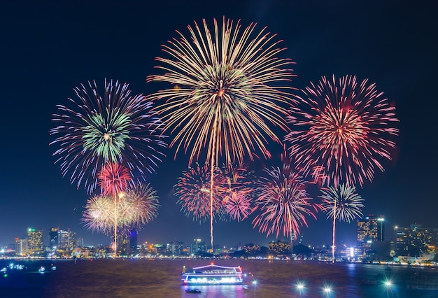Fogos de artifício sobre a paisagem urbana pela praia no crepúsculo a noite