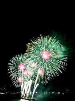 Fogos de artifício verdes e rosa no céu noturno