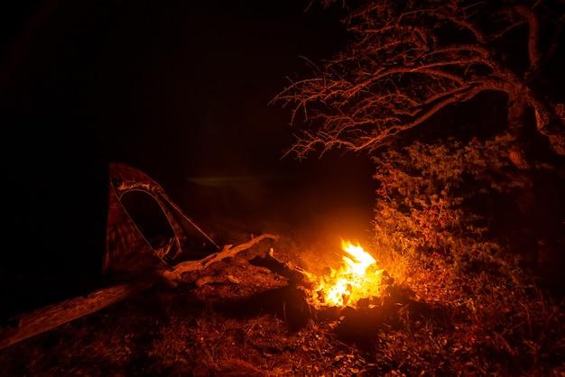 Fogueira brilhante perto da tenda à noite em um acampamento turístico