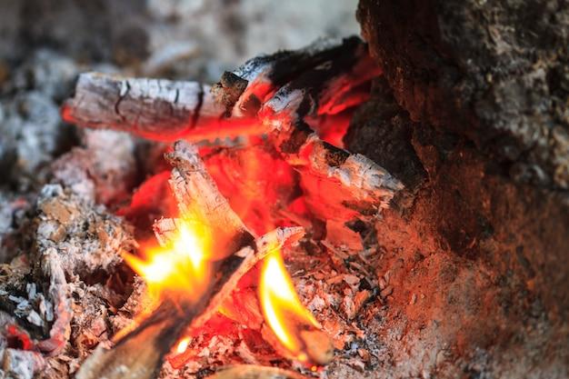 Fogueira com chamas laranja e lenha