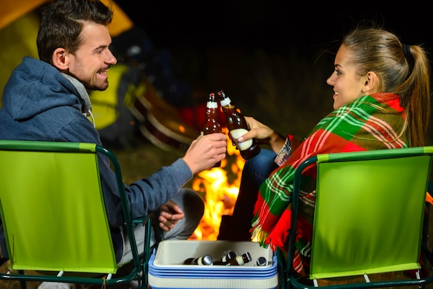 Fogueira de casal enquanto acampar bebendo cerveja