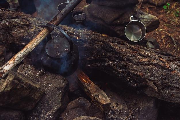 Fogueira extinta com chaleira em lenha grande