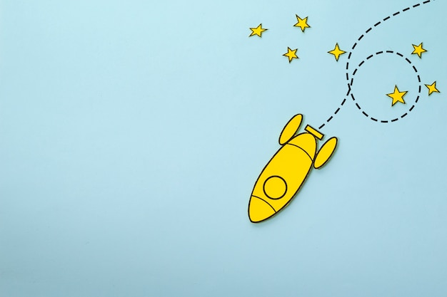 Foguete amarelo pequeno loop em torno de estrelas sobre um fundo azul