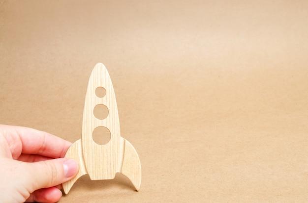 Foguete de madeira à disposição em um fundo branco. um homem está brincando com um foguete.