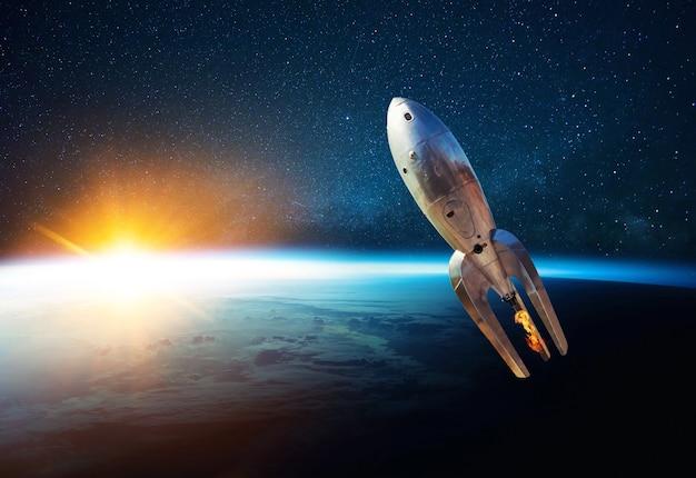 Foguete de metal vintage com fogo decola em espaço aberto estrelado perto do planeta terra com o pôr do sol. a nave espacial retro decola e voa em um fundo de céu estrelado, planeta e luz do sol