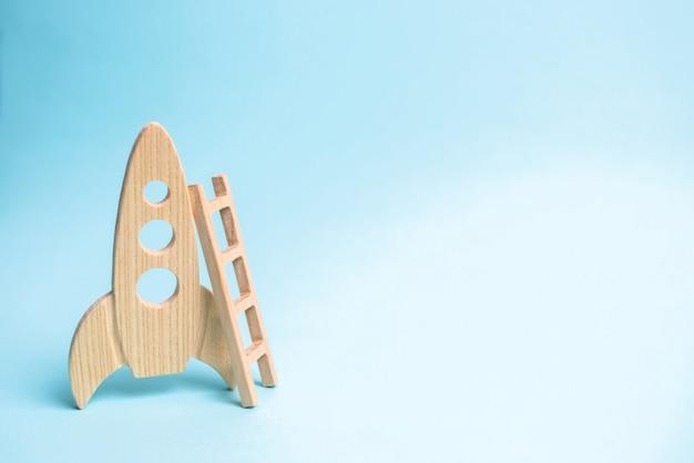 Foguete e escada em um fundo azul. o foguete está pronto para decolar no espaço.