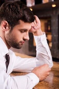 Foi o pior dia de todos. jovem deprimido de camisa e gravata encostado no balcão do bar e olhando para dentro do copo