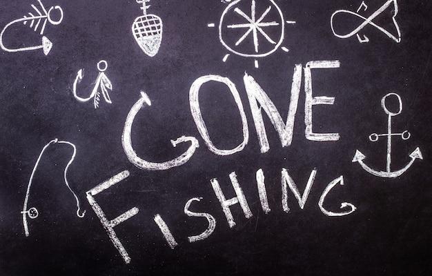 Foi pescar com inscrição de giz na lousa com desenhos marinhos