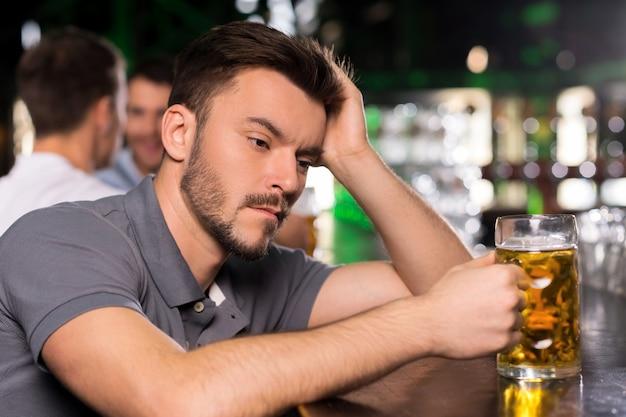 Foi um dia difícil. jovem deprimido bebendo cerveja em bar e segurando a mão no cabelo