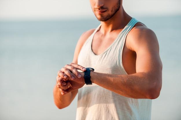 Foi um ótimo treino. imagem recortada de jovem homem musculoso verificando as horas em seus relógios enquanto está ao ar livre