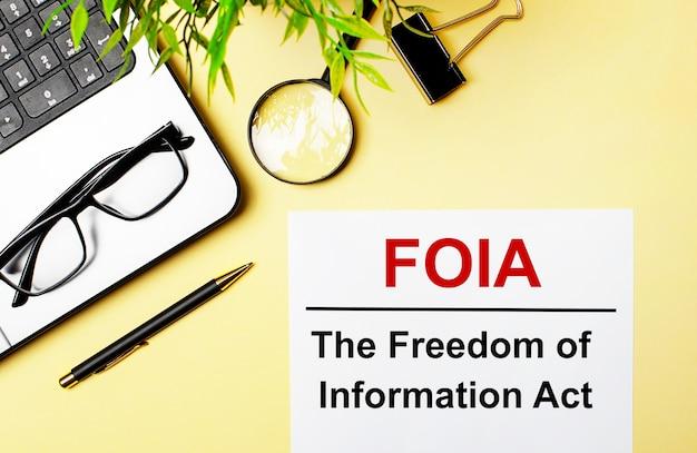 Foia a lei de liberdade de informação está escrita em vermelho em um pedaço de papel branco em uma superfície amarela clara ao lado de um laptop, caneta, lupa, óculos e uma planta verde