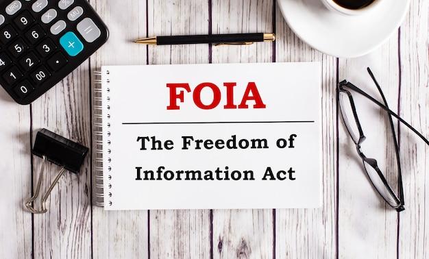 Foia o freedom of information act é escrito em um bloco de notas branco perto de uma calculadora, café, óculos e uma caneta