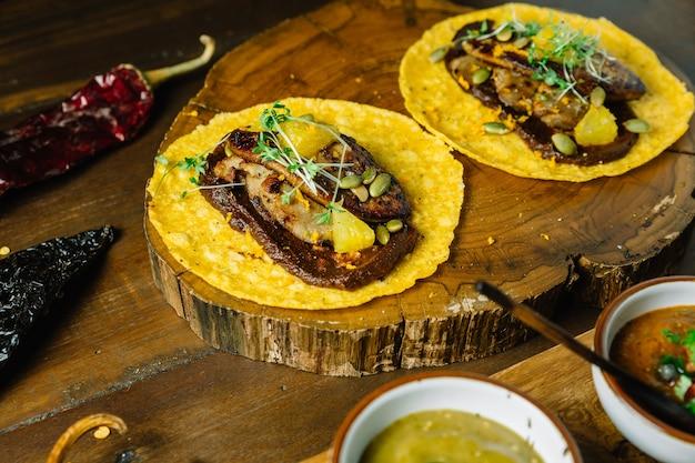 Foie gras tacos servido em tábua de madeira com diferentes molhos
