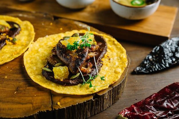 Foie gras tacos servido na tábua de madeira.