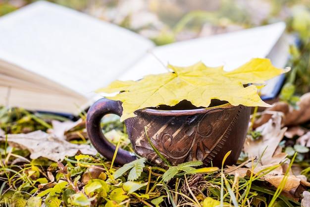 Folha amarela de bordo em uma xícara de café perto do livro aberto na floresta de outono