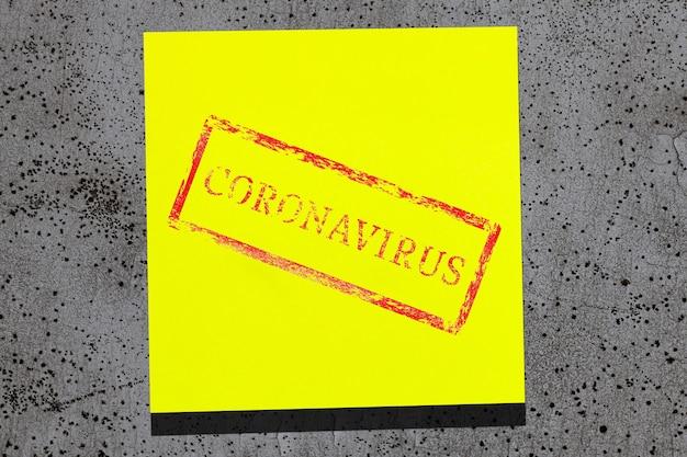 Folha amarela pegajosa com coronavírus escrito na parede de pedra cinza