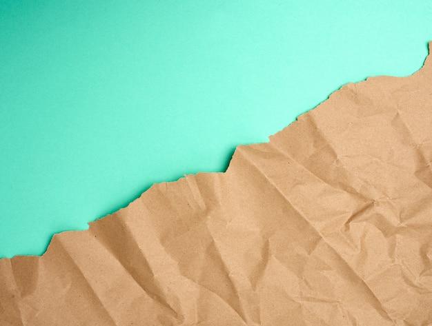 Folha amassada de papel de embrulho marrom sobre um fundo verde