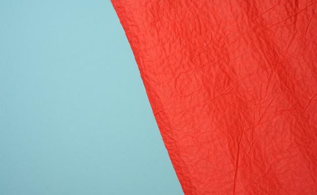 Folha amassada de papel vermelho sobre fundo azul, vincos e arranhões. lugar para inscrição, full frame