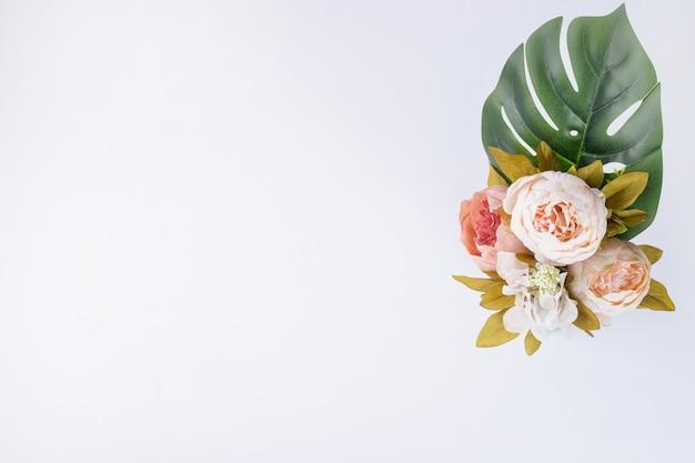 Folha artificial e buquê de flores na superfície branca.