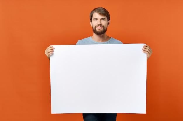 Folha branca de papel anúncio anúncio homem no cartaz de maquete de fundo laranja de fundo. foto de alta qualidade