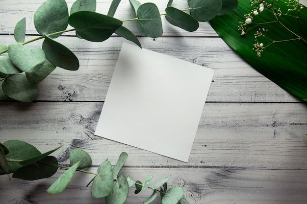 Folha branca em branco com lugar para texto em um fundo claro com folhas de plantas, flores e eucalipto