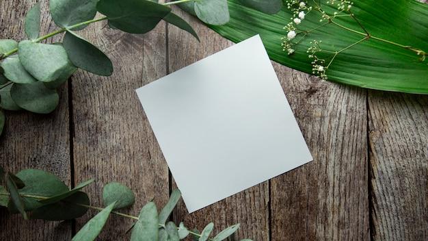 Folha branca em branco com lugar para texto em um fundo de madeira marrom com folhas de plantas, flores e eu