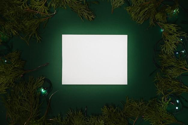 Folha branca em fundo verde de natal com galhos e luzes