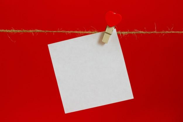 Folha branca para anotações em um fundo vermelho com um prendedor de roupa com um coração em uma corda de chicote para inscrições