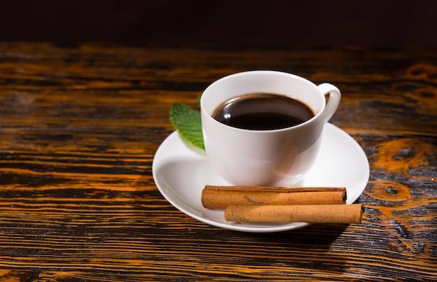 Folha com chá preto na xícara e pires ao lado de um par de paus de canela sobre a mesa de madeira