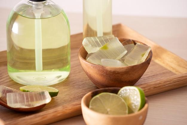 Folha de babosa, tigela cheia de babosa descascada, limão e frascos de gel de babosa ou infusão