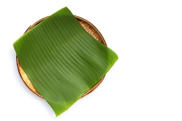 Folha de banana na cesta de bambu em fundo branco.