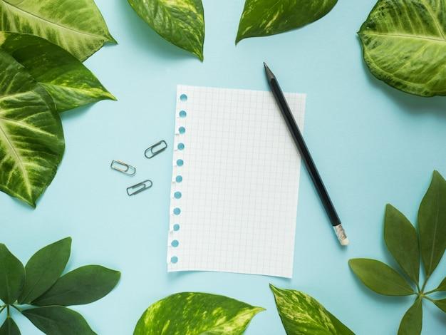 Folha de bloco de notas com lápis no centro sobre fundo azul com folhas verdes