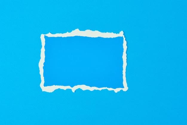 Folha de borda rasgada de papel rasgado em fundo azul. molde com pedaço de papel colorido