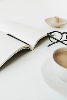 Folha de caderno, caneta, óculos, xícara de café na superfície branca