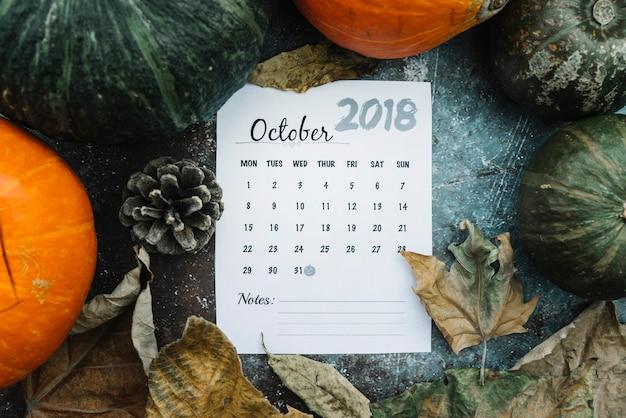 Folha de calendário com data de halloween em abóboras e folhas