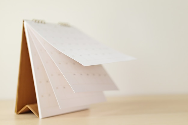 Folha de calendário de borrão virando folha em mesa de madeira
