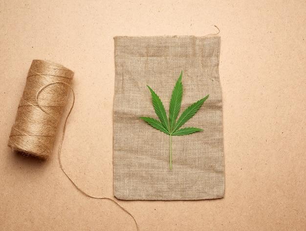 Folha de cânhamo verde, novelo com corda marrom e saco vazio em um fundo de madeira marrom