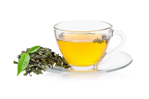 Folha de chá verde com um copo de chá no fundo branco