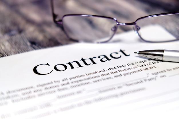 Folha de contrato com óculos e uma caneta em um fundo de madeira