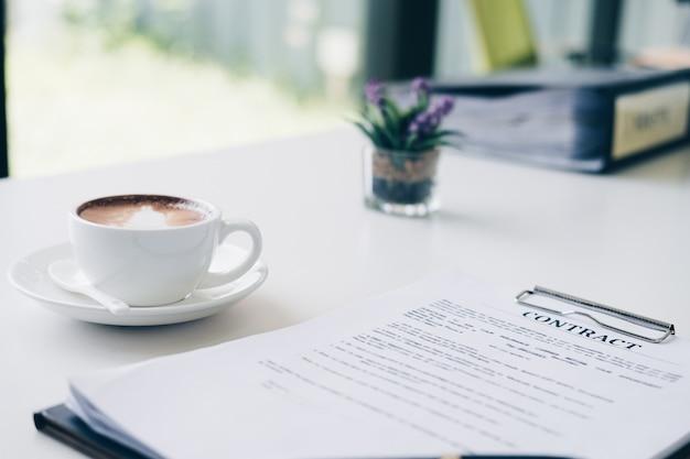 Folha de documento de contrato e documento de negócios, perto de arte de latte de xícara de café no escritório em casa