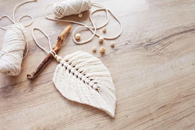 Folha de macramé em cor natural e enrolamentos de linha sobre uma mesa de madeira. macramê de decoração em corda de algodão para deixar seu ambiente mais aconchegante e exclusivo. passatempo feminino. decoração de tapeçaria artesanal. copie o espaço