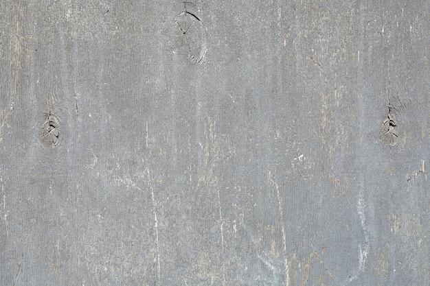 Folha de madeira compensada, pintada na cor cinza claro, limpa e riscada.