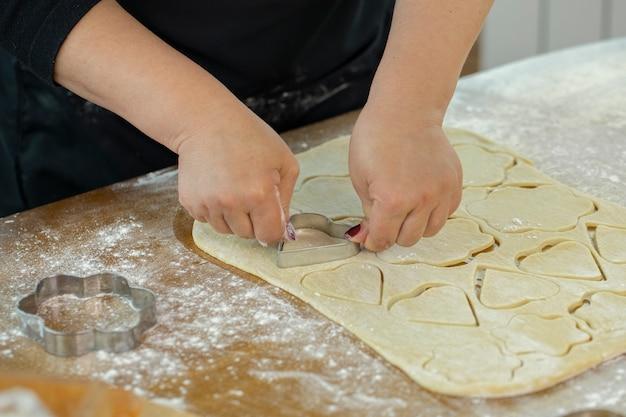 Folha de massa de fatias de mão de mulher com molde de biscoito em forma de coração e flores para biscoitos caseiros na aula de cozinha. conceito de tradições familiares. conceito de aula de panificação caseira