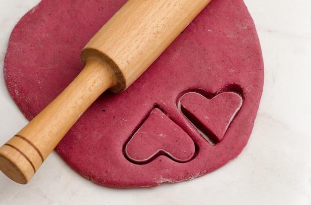 Folha de massa vermelha com um rolo e corte dois biscoitos em forma de coração, preparando-se para o dia dos namorados
